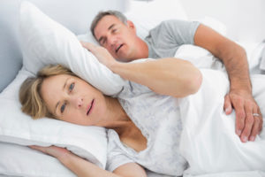 A wife blocking the sound of her husband's snoring