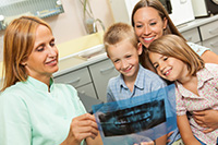 A dentist showing a dental x-ray to a family